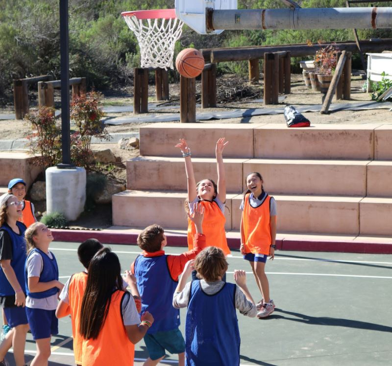 Middle school students playing basketball during PE class